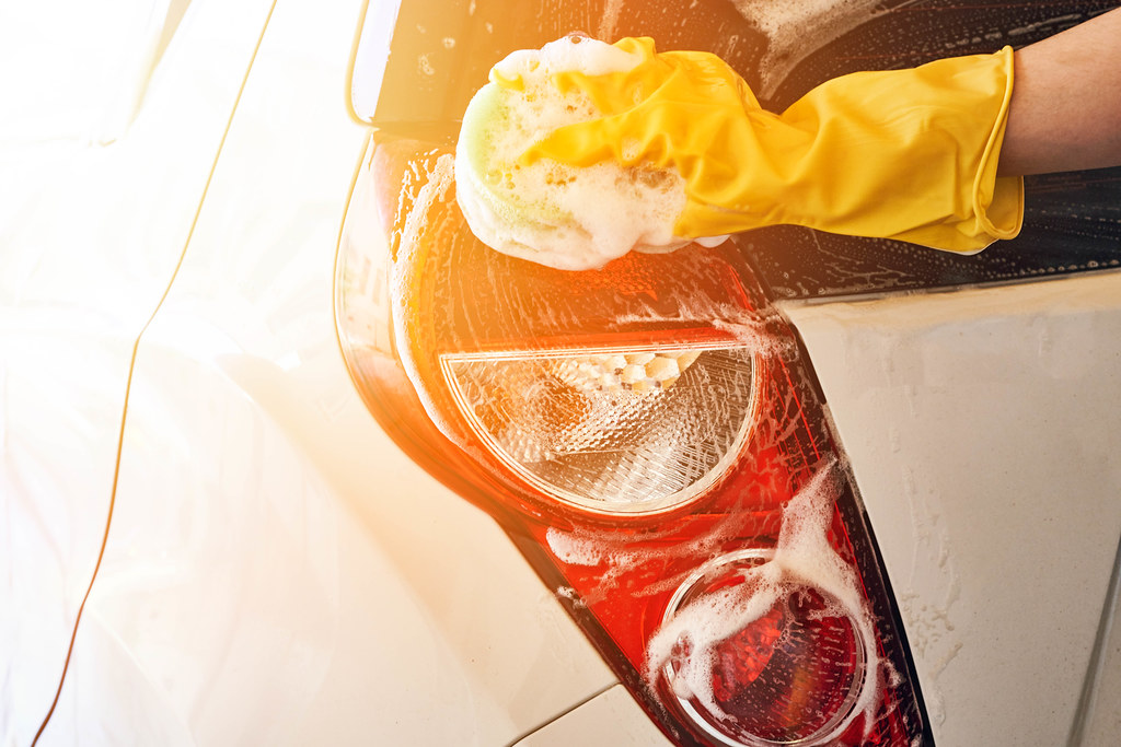 Man washing car rear lights with sponge and foam