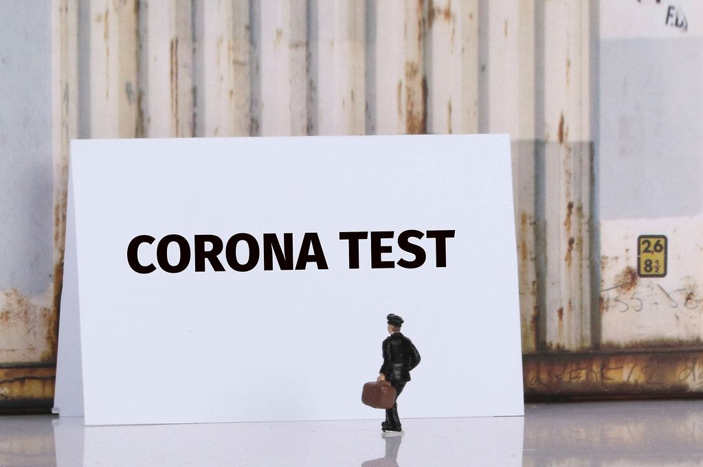 Man with a suitcase standing in front of Corona test text