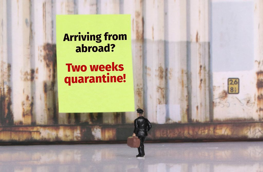 Man with a suitcase standing in front of yellow board with Two weeks quarantine warning