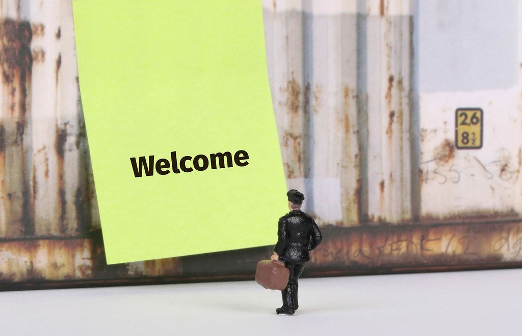 Man with a suitcase standing in front of yellow board with Welcome text