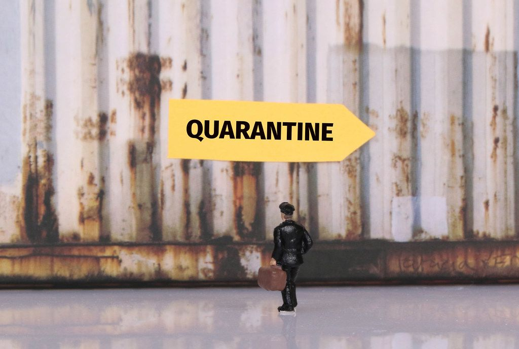 Man with a suitcase standing in front of yellow sign for Quarantine
