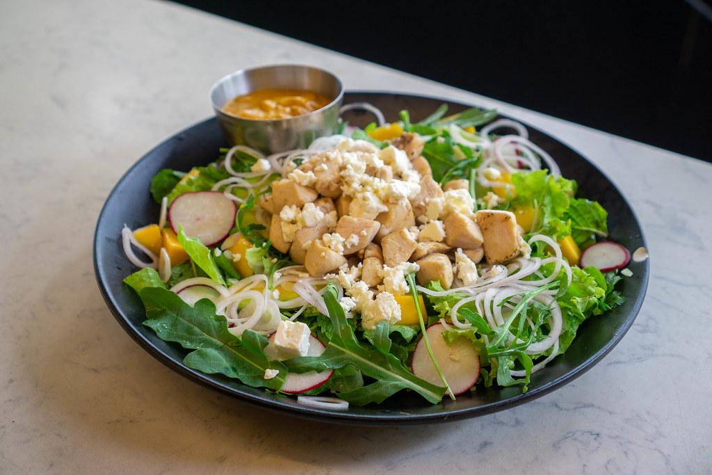 Mango-Curry-Hähnchen Salat mit Rucola, Feta Käse, Avocado, Radieschen und Zwiebeln auf einem Teller in einem Restaurant