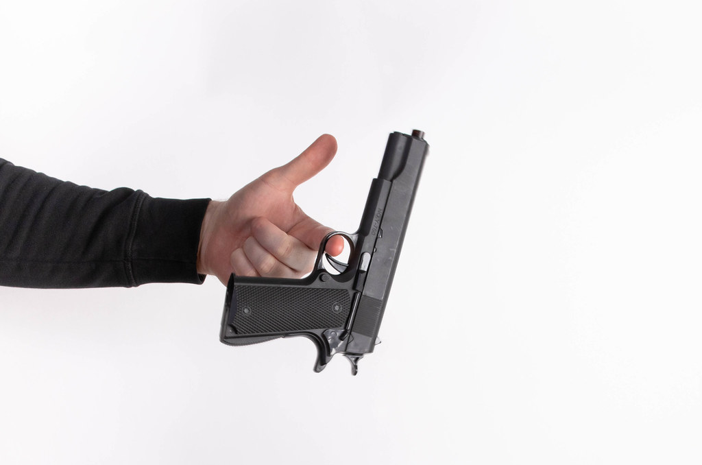 Man's hand holding gun, isolated on white