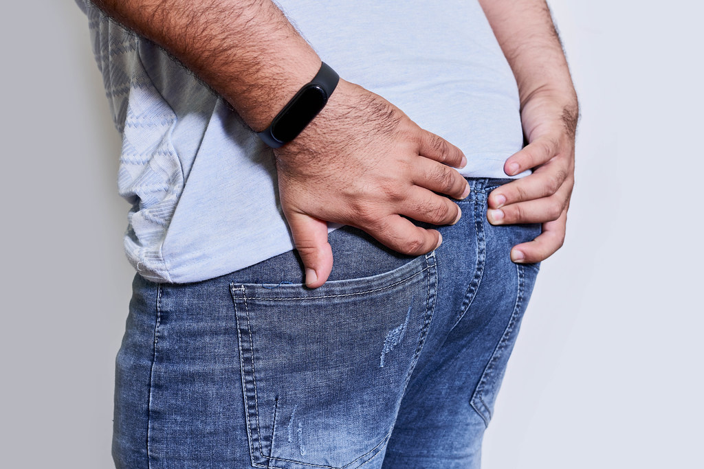 Man's hand holding his bottom because having abdominal pain and hemorrhoids - Health care concept