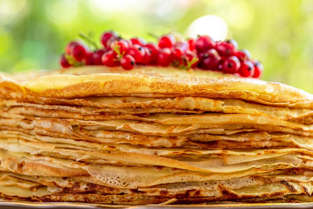 Many pancakes are stacked with fresh red currant berries on a blurred bokeh nature background