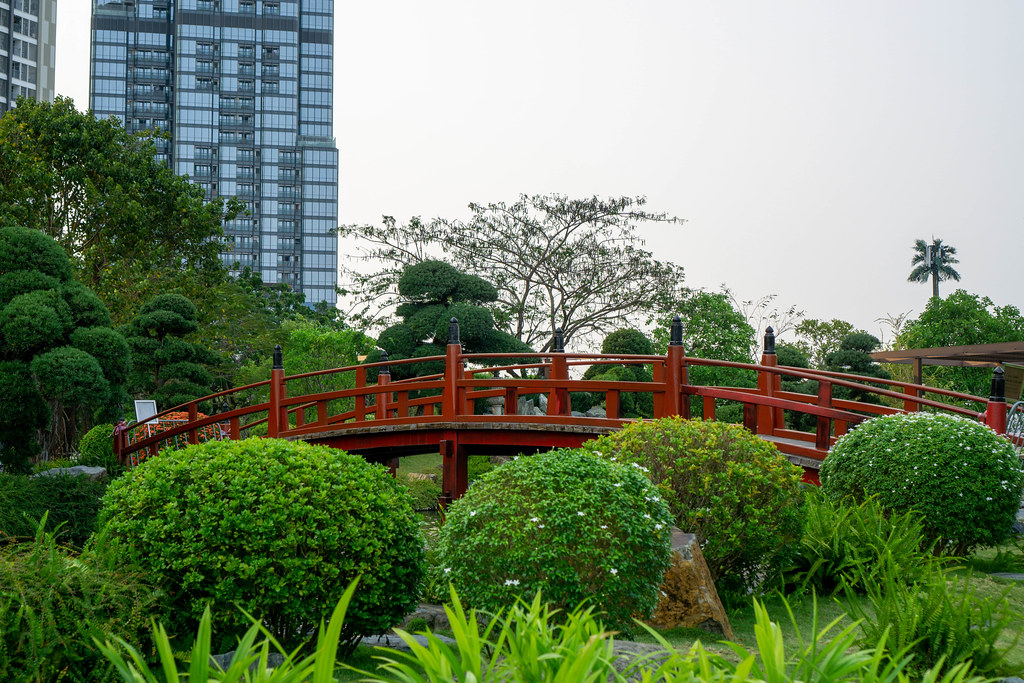 Many Plants and Flowers around a Red Wooden Bridge over a Fish Pond with Vincom Landmark 81 Skyscraper in the Background at Vinhomes Central Park in Saigon, Vietnam