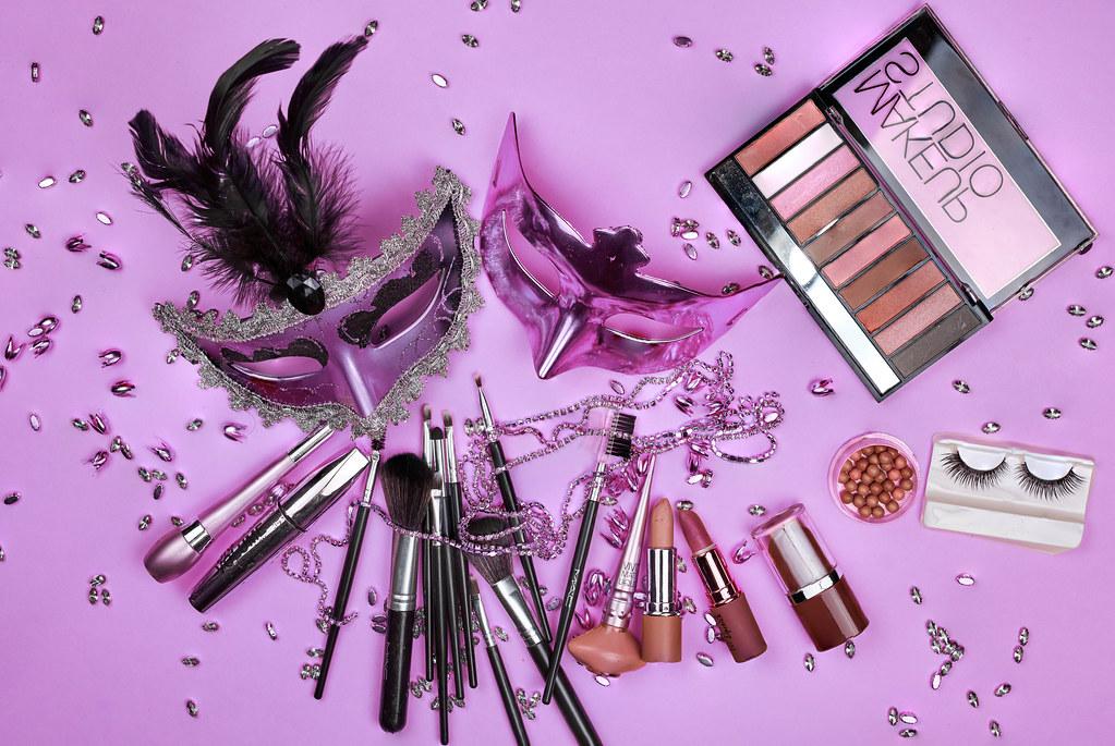 Mardi Gras carnival masks and female make-up tools set on purple background