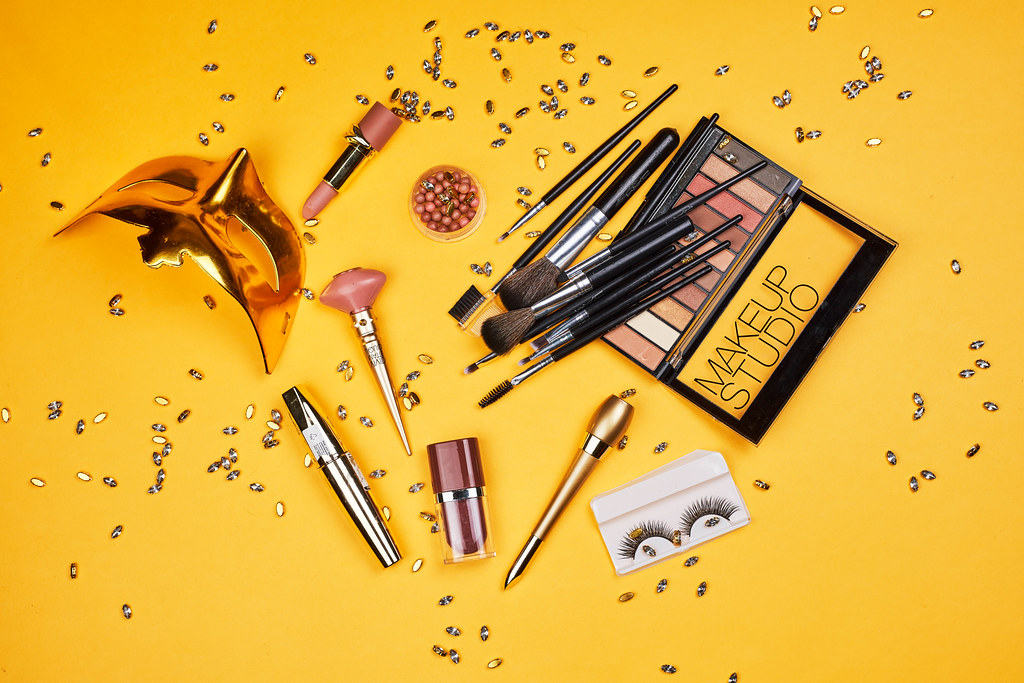 Mardi Gras mask and carnival make-up tools on yellow