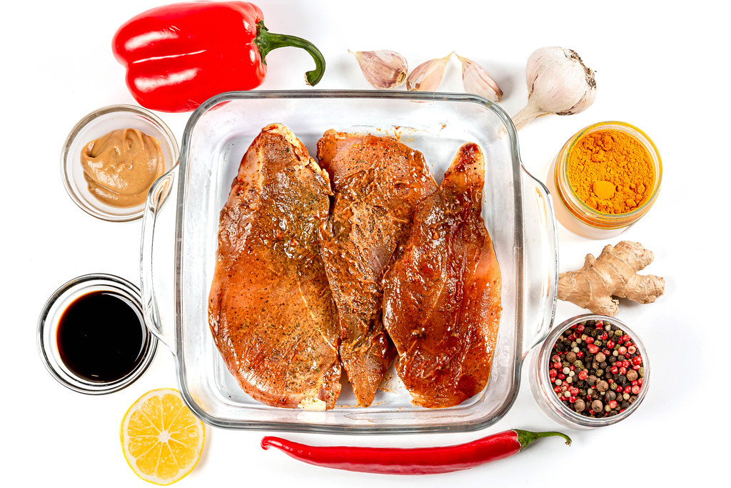 Marinated chicken fillet with spices in a glass baking sheet, top view