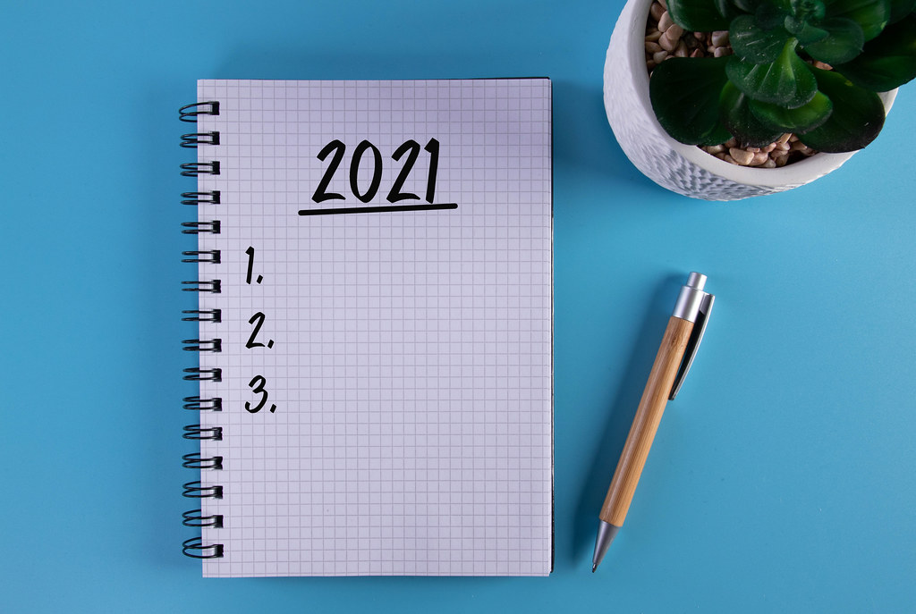 Marker and notebook with 2021 To do list on blue background