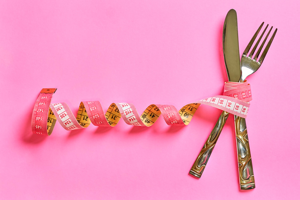 Measuring tape with spoon and fork on pink background