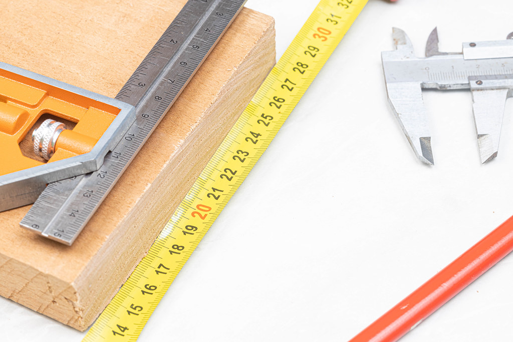 Measuring tools on the wooden board above white background