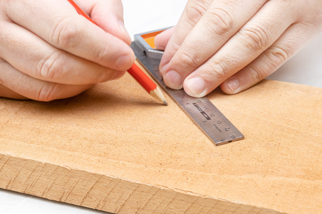 Measuring wooden board with measuring tool and pencil