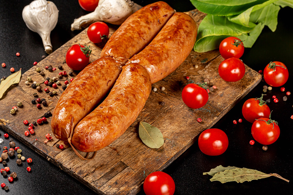 Meat sausages with spices on an old wooden kitchen board