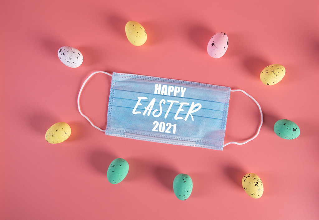 Medical face mask and colorful easter eggs with Happy Easter 2021 text