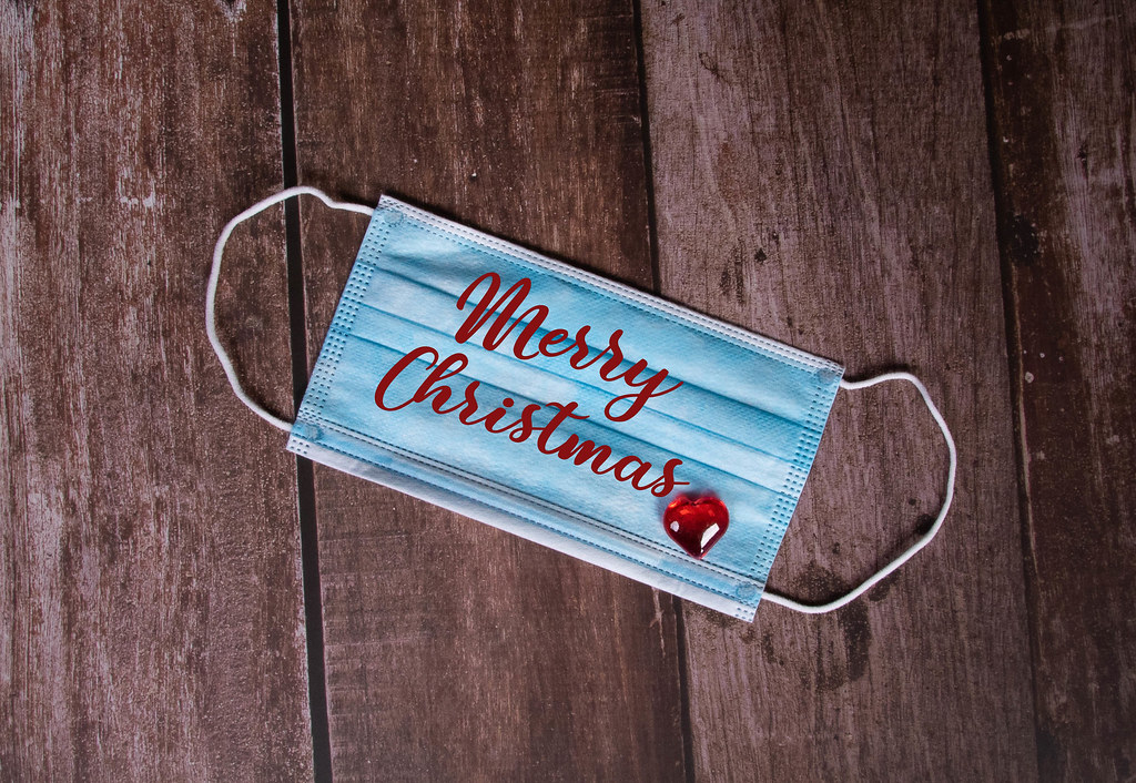Medical face mask with Merry Christmas text on wooden background