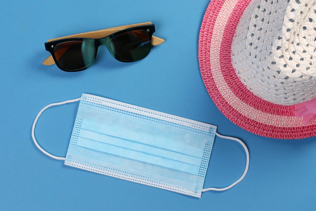 Medical face mask with sun hat and sunglasses on blue background