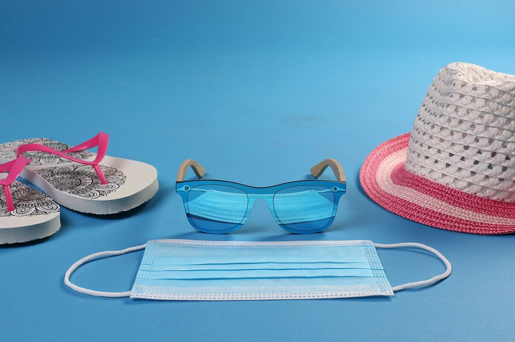 Medical face mask with sun hat, flipflops and sunglasses on blue background