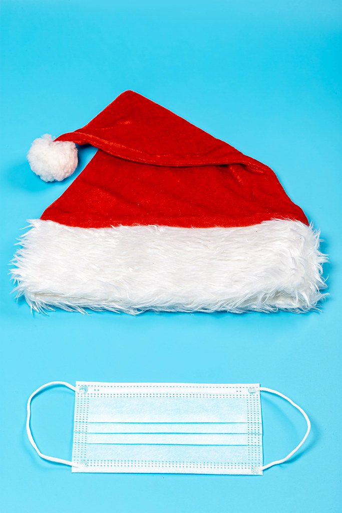 Medical mask and santa claus cap on blue background, top view