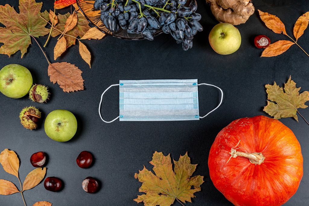 Medical mask on an autumn background with a pumpkin. Personal protection concept in autumn season