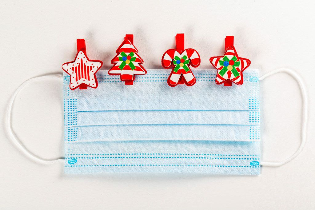 Medical mask with multicolored christmas wooden clothespins on white
