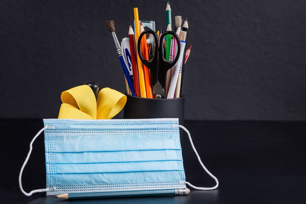 Medical mask with school supplies, bell and yellow ribbon on a black background