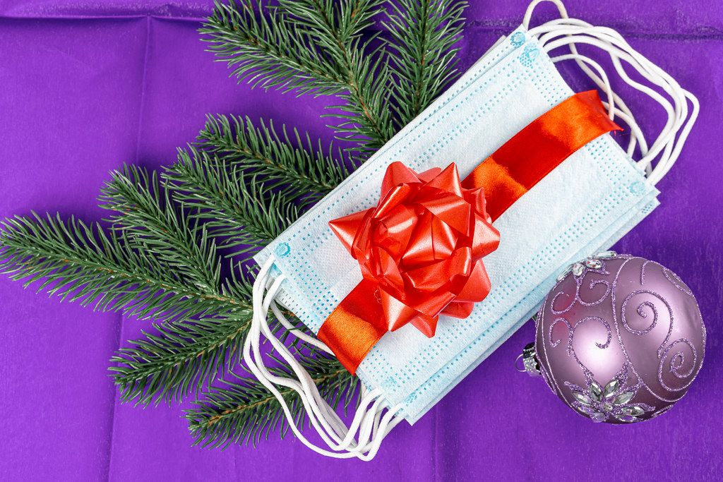 Medical protective face masks with red gift ribbon, Christmas ball and fir branches on a purple background