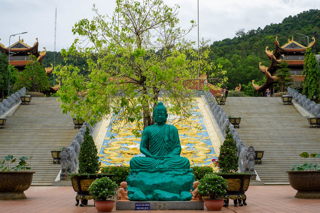 Meditating Buddha Statue with Trees and Plant Pots in front of large Golden Dragon carved in Stone at Truc Lam Ho Quoc Zen Monastery in Phu Quoc, Vietnam