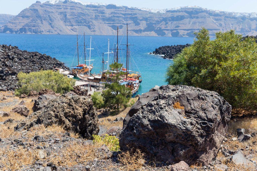 Mediterrane Landschaft auf dem griechischen Insel Santorini mit Meer, Klippen, Pinien und Segelbooten