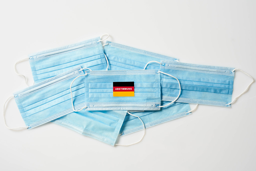 """Medizinische Gesichtsmasken mit deutscher Flagge und Schrift """"Abstimmung"""": Wahl in Corona-Zeit"""