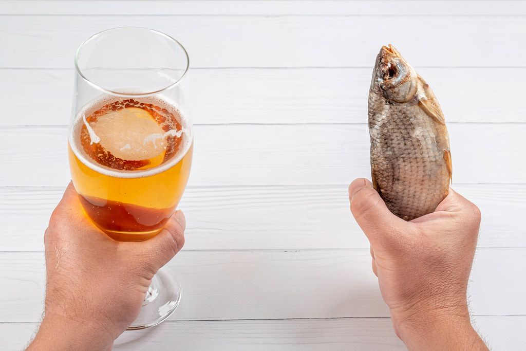 Men's hands with beer and dried fish