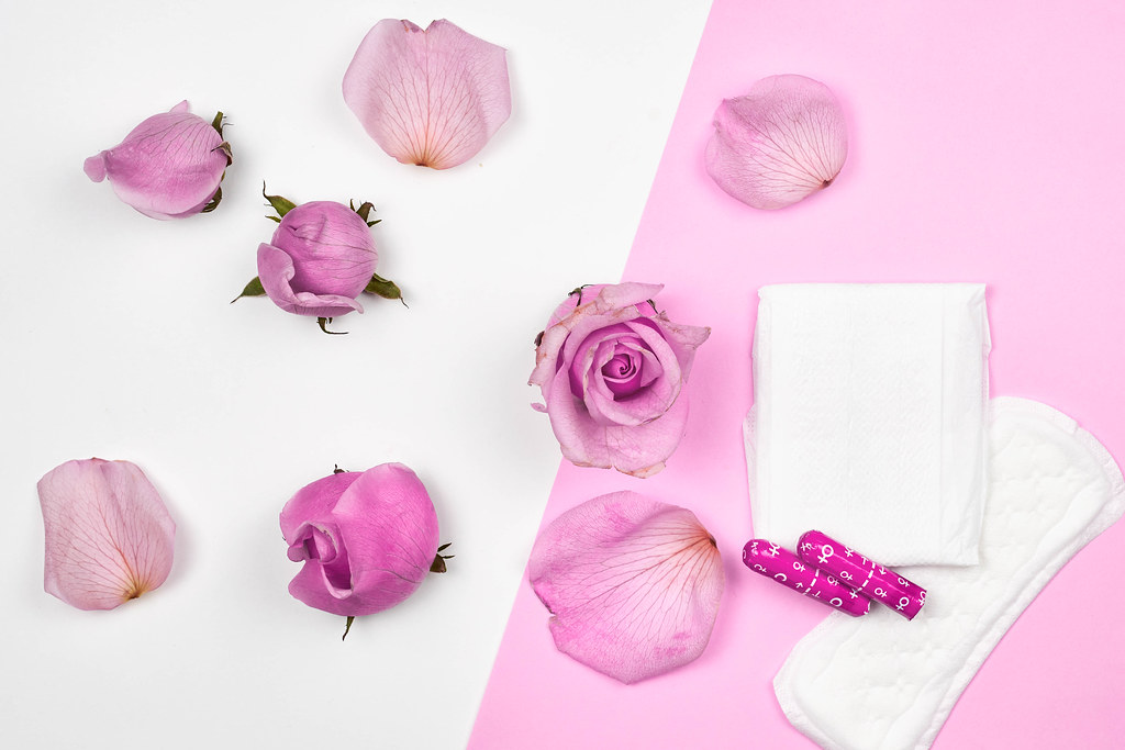 Menstrual cycle products: sanitary pad, panty liner and tampons on a pink-white background with roses