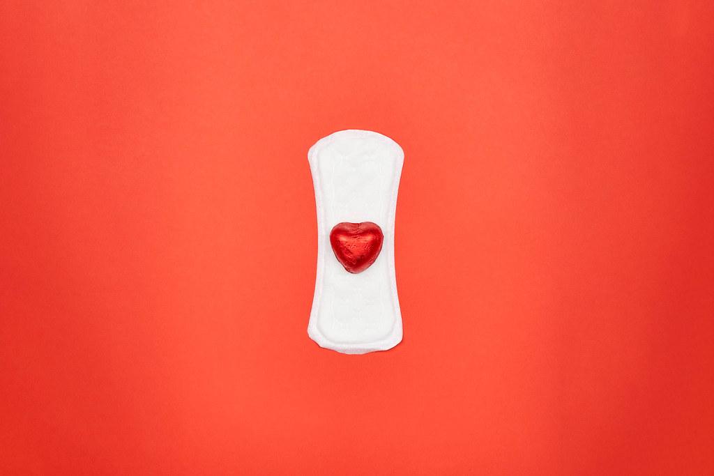Menstruationsprodukte: eine Binde mit einem roten Schokoherz in der Mitte vor rotem Hintergrund