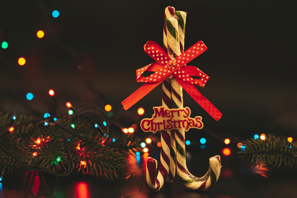 Merry christmas background with lollipops cane on background of colorful garland bokeh