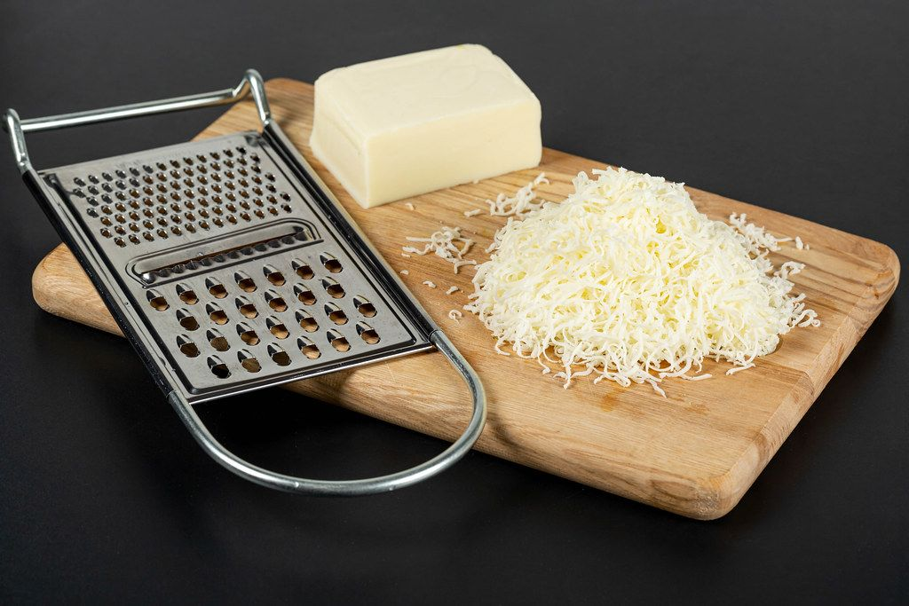 Metal cheese grater and mozzarella cheese on kitchen board