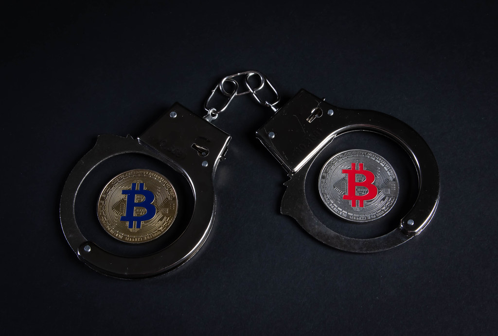 Metal handcuffs and silver and golden Bitcoin coin