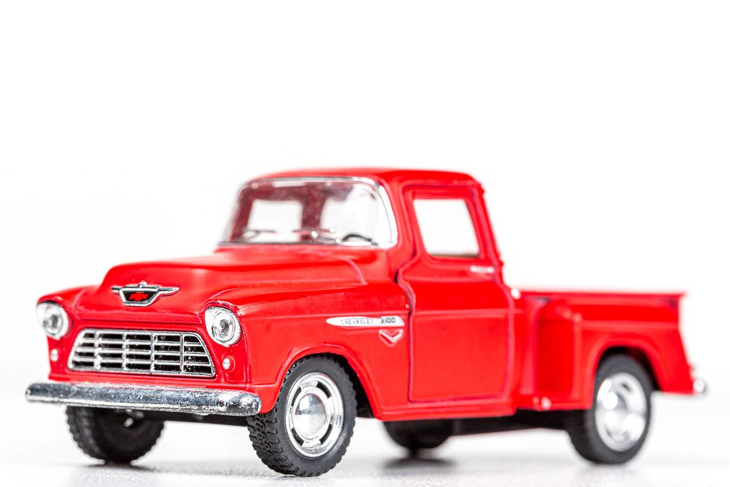 Metal model of a red pickup truck on a white background