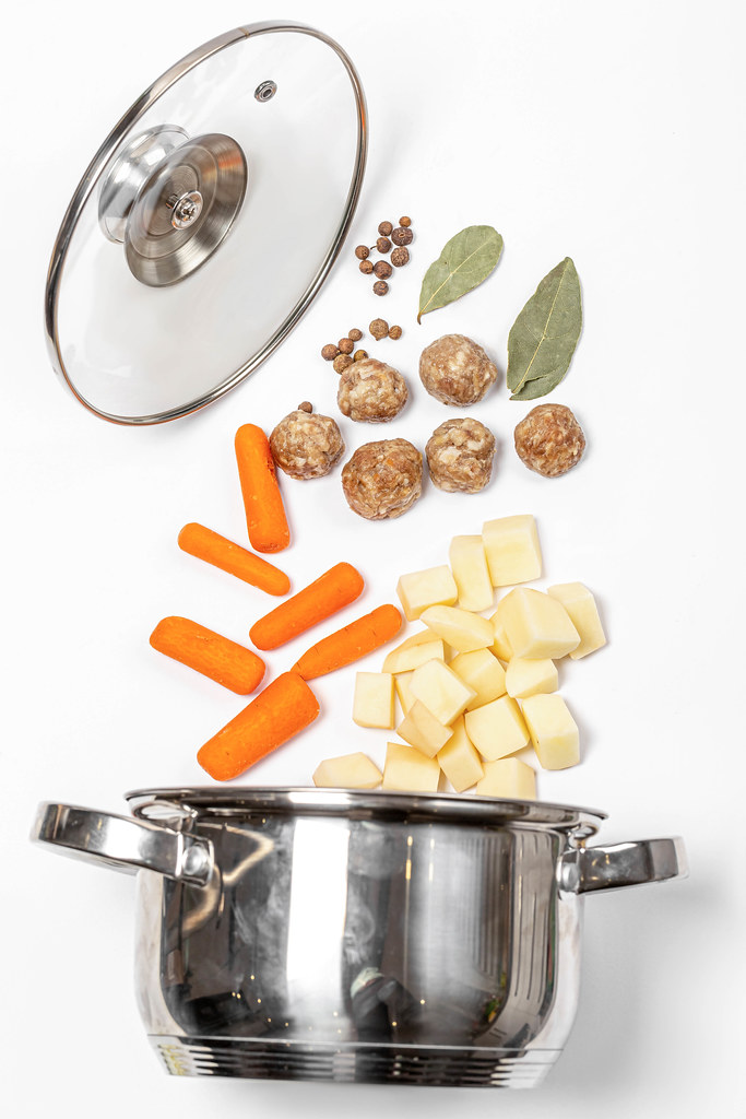Metal saucepan with lid and raw ingredients for making soup