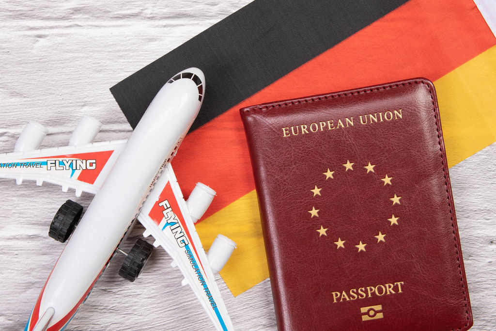 Miniature airplane and passport over flag of Germany