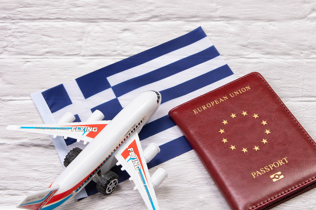 Miniature airplane and passport over flag of Greece