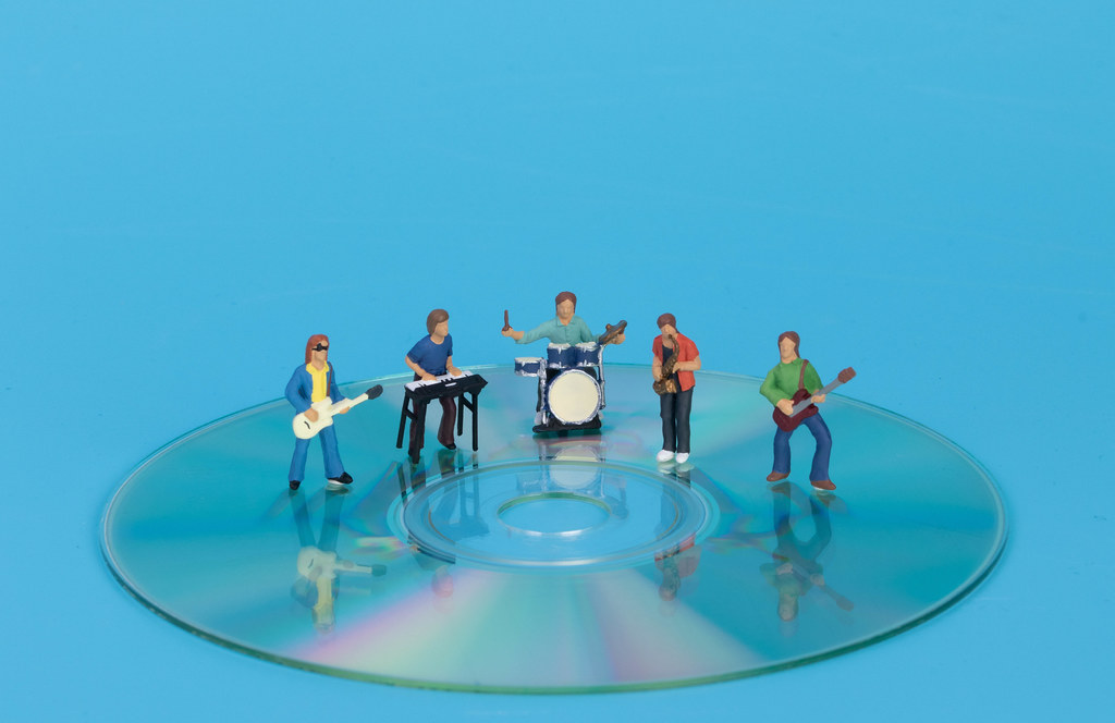 Miniature band standing on CD