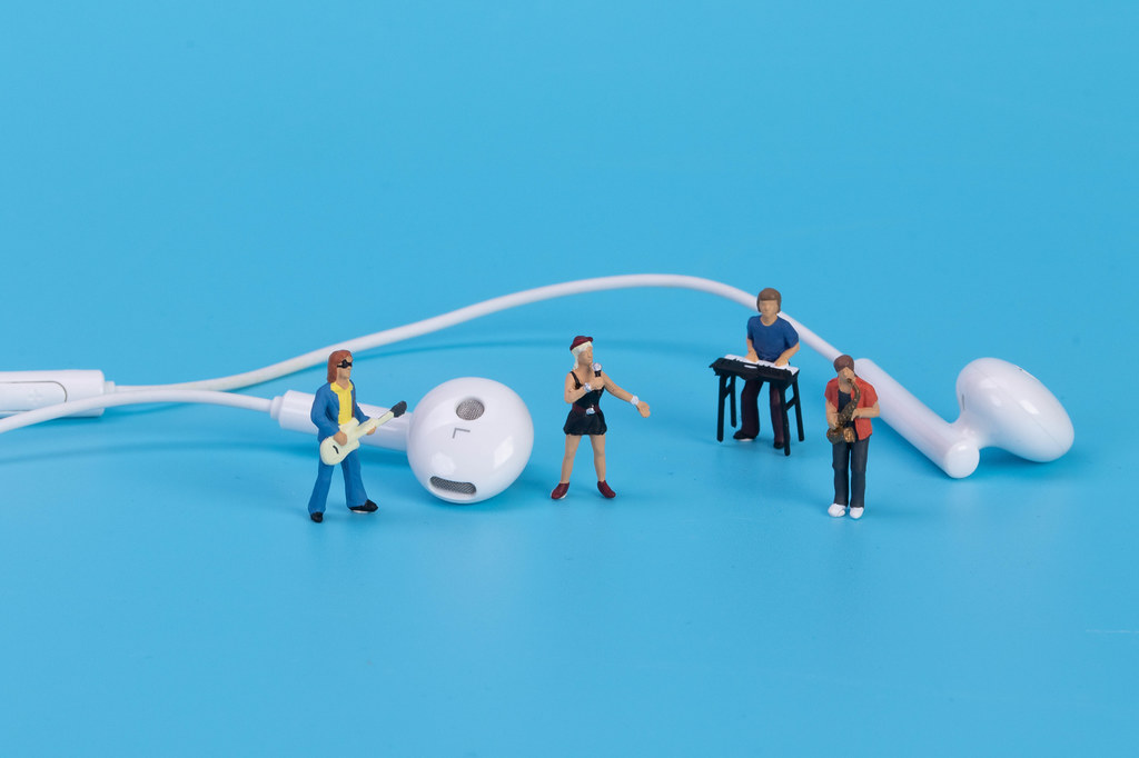 Miniature band with earbuds on blue background