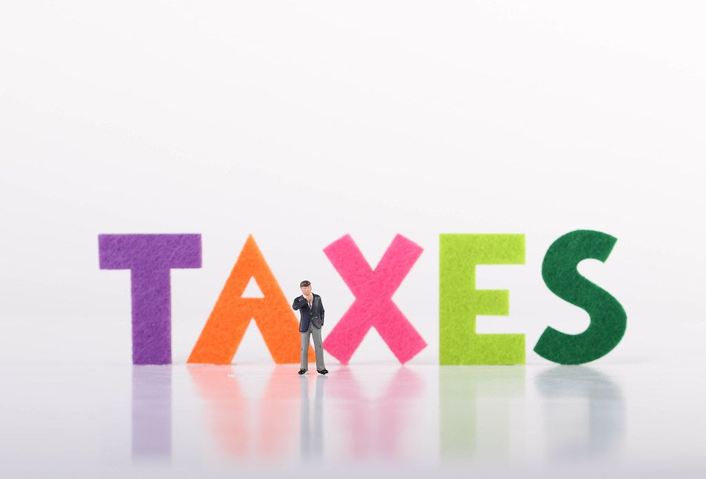 Miniature businessman standing in front of Taxes text on white background