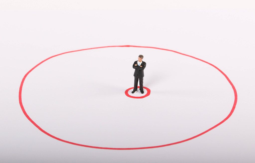 Miniature businessman standing in red circle