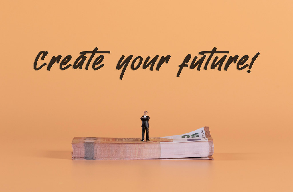 Miniature businessman standing on a stack of Euro money with Create your Future text