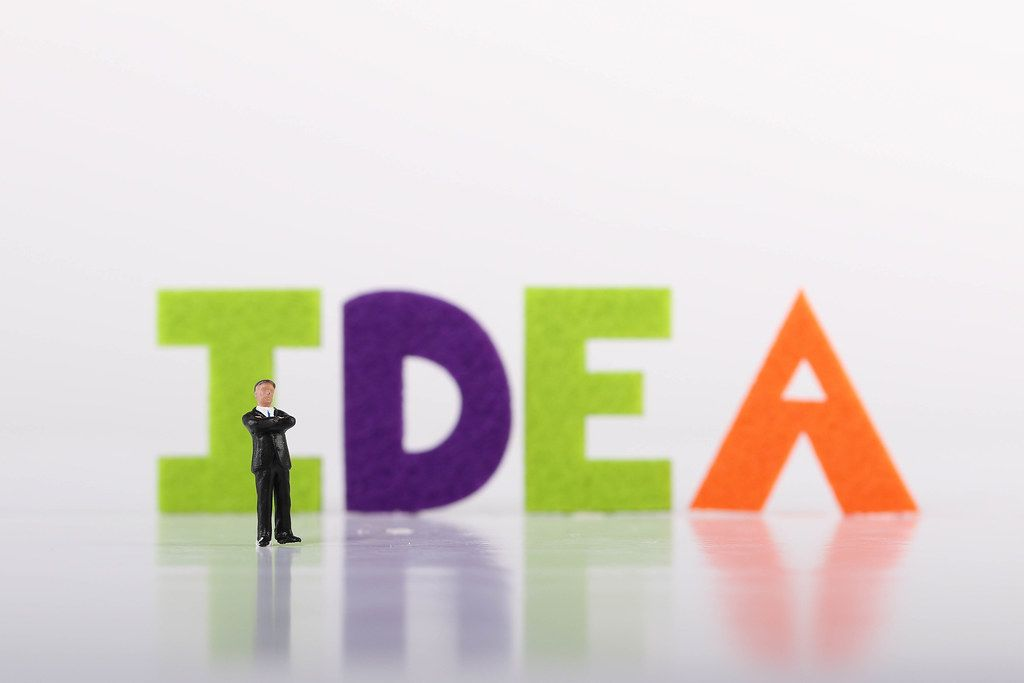 Miniature businessman with Idea text on white background