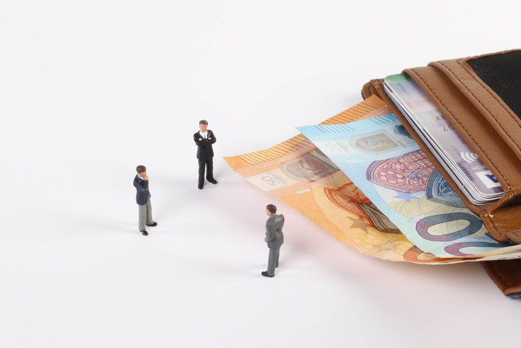 Miniature businessman with open wallet and Euro banknotes