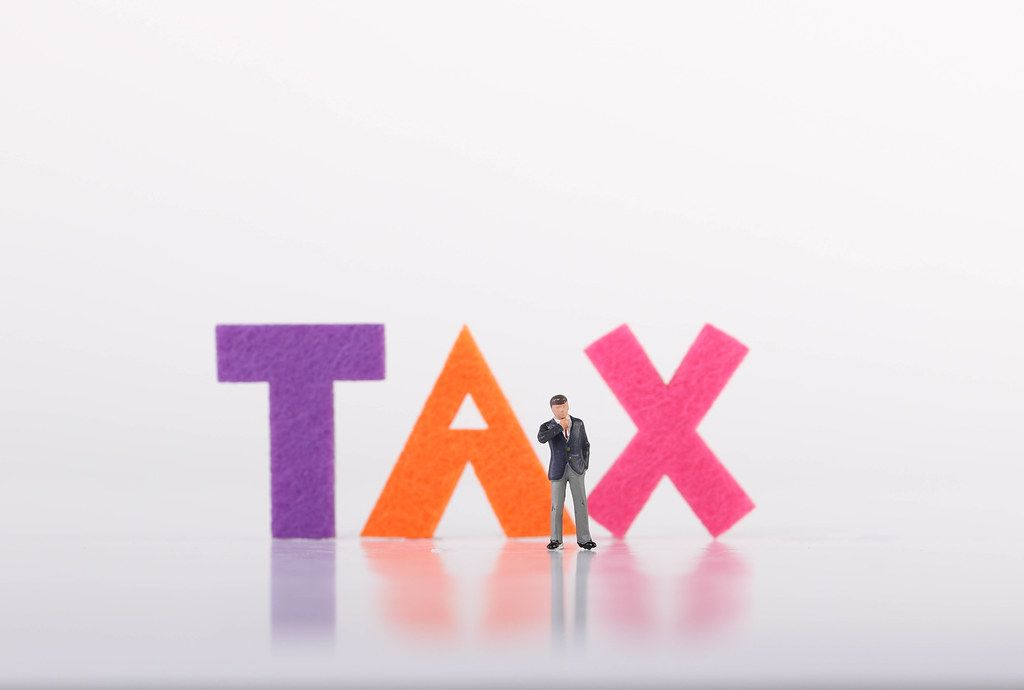 Miniature businessman with Tax text on white background
