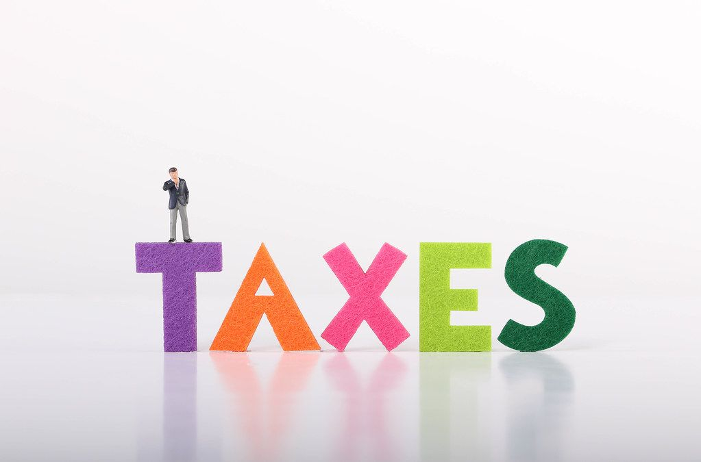 Miniature businessman with Taxes text on white background