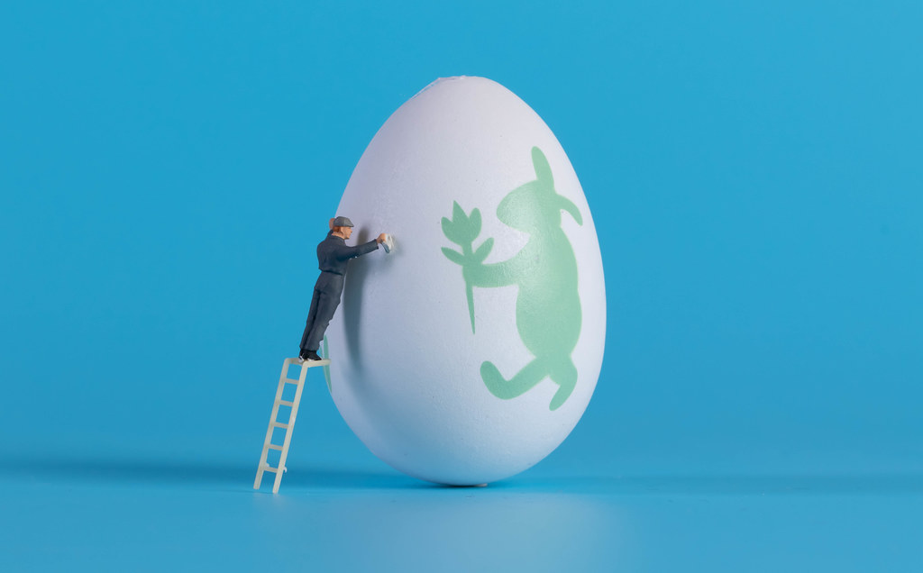 Miniature cleaner cleaning easter egg on blue background